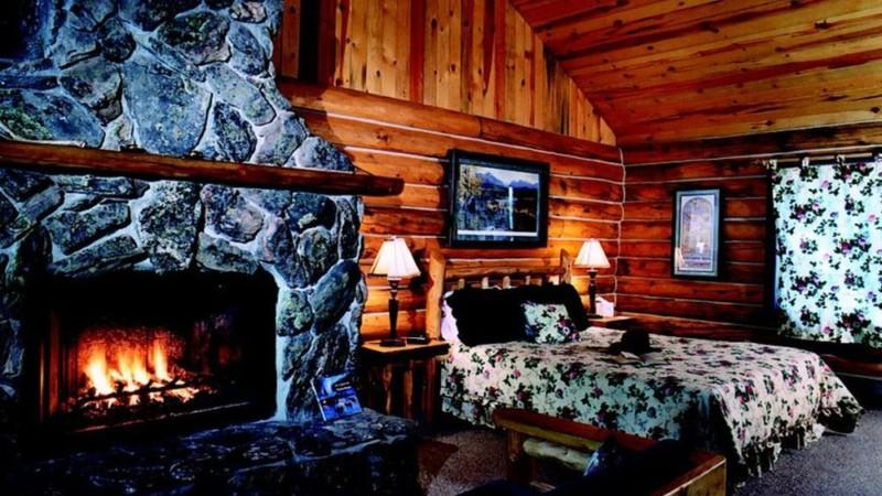 Log cabin designed bedroom with fireplace
