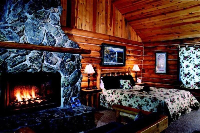 Log cabin designed bedroom with fireplace