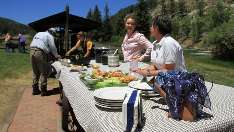 Staff prepare a wonderful lunch on a picnic table near the South Platte River