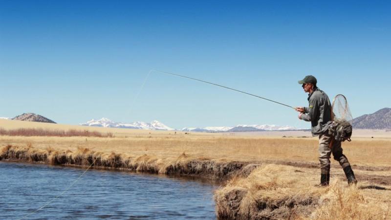 Angler casts a fly rod from the bank of a mountain river