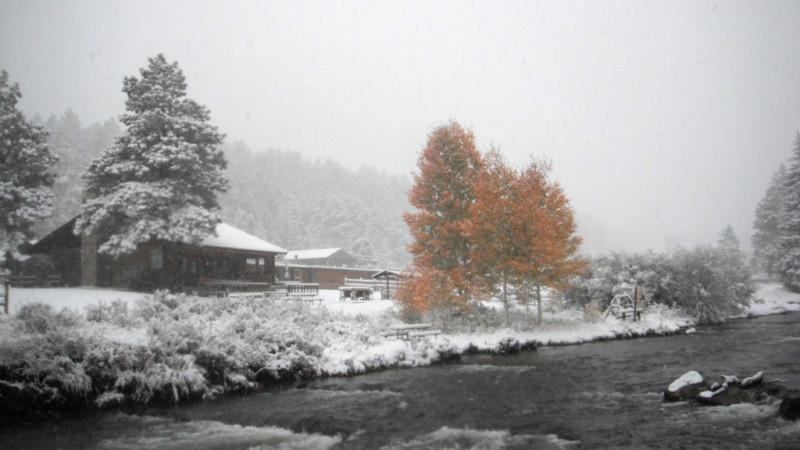 Snow-covered buildings along a mountain stream